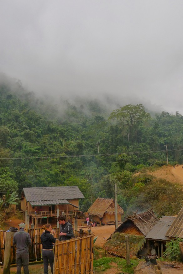 Early morning on day 2 of trekking: fog crawls over the mountain walls that surround us. In the foreground, the bamboo structure you can glimpse is the communal village shower where everyone washes, covered in sarongs for modesty.