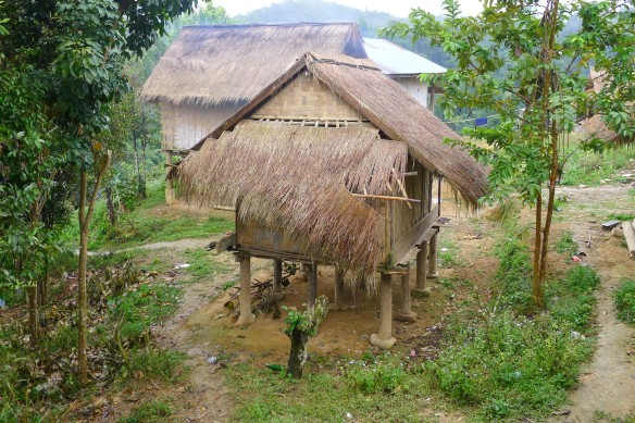 A typical village house in Laos - on stilts due to the possibility of floods or mud slides and for protection from animals, covered with a thatched roof.